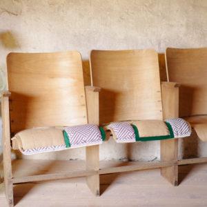 Fauteuils de cinéma vintage en bois des années 50, assise retapissée avec toile de jute, tissu au motif graphique, ponctuée de velours vert pour un esprit industriel et tribal.