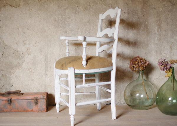 fauteuil vintage patiné en blanc et tapissé d'une toile de jute ancienne associé à une dame Jeanne et à une vieille valise rose