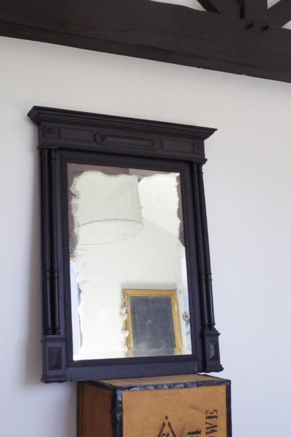 Ce miroir ancien en bois sculpté est mercurisé et son tain est largement patiné sur les pourtours.