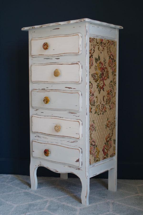 Semainier ancien rénové, poignées et côté en velours, motifs floraux et tonalités douces.