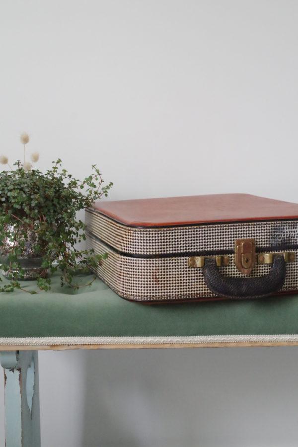 Cette petite valise ancienne est en carton bouilli protégé par un revêtement en vinyle aux motifs pieds-de-poule noirs et blancs.