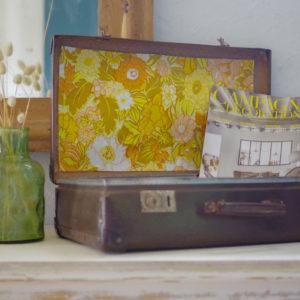 Datant des années 50-60, cette valise vintage en fibre vulcanisée dégage un charme rétro indéniable avec son intérieur tapissé d'un papier peint vintage.