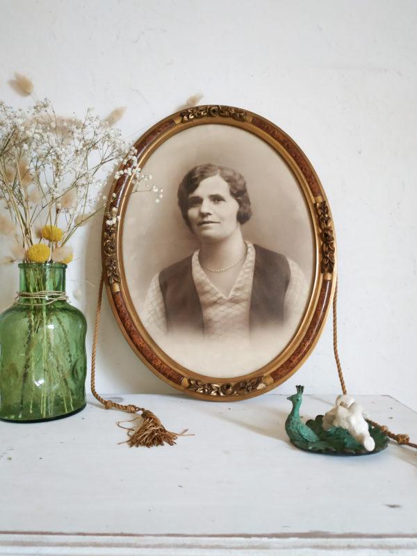 Voici un portrait de femme du début du siècle dernier dans un cadre en forme de médaillon.