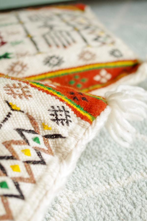 Ce coussin vintage réalisé à la main arbore avec délicatesse des broderies contrastantes ikat, aux motifs singuliers et colorés.