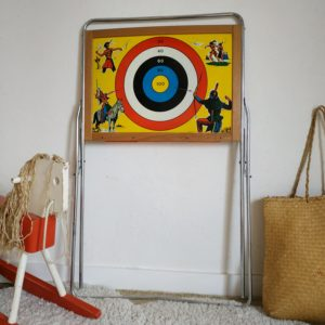 Tableau ardoise d'un côté avec boulier pour compter et jouer au maître et à la maîtresse, ce jouet propose également côté verso une cible en tôle joliment peinte représentant des indiens.