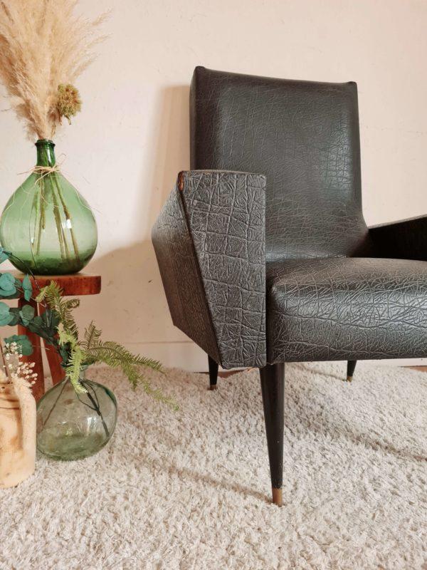 Ce fauteuil est perché sur une structure en métal tubulaire laquée noir.