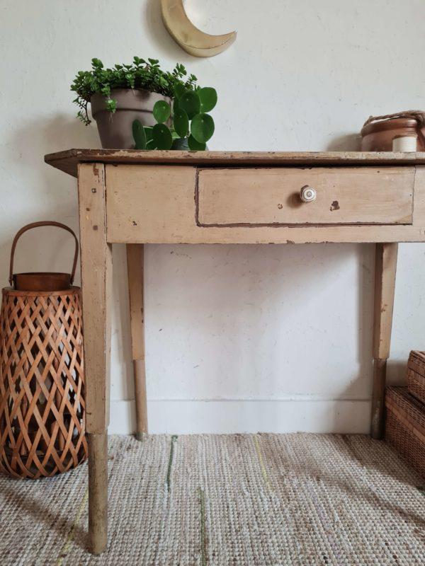 Cette ancienne table revêt une coloris beige taupe subtilement patiné et possède un tiroir.