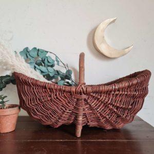Ce panier ancien est réalisé à partir de fibres d'osier et possède une anse en bois courbé.