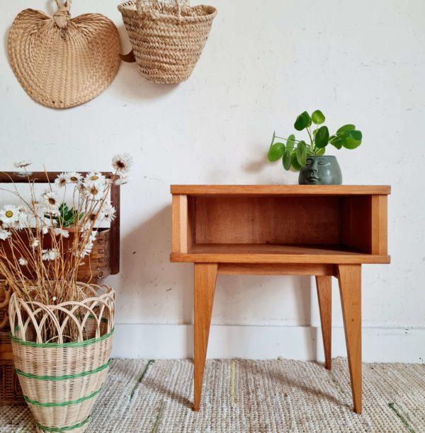 Ce chevet en bois et rotin vintage arbore une teinte miel.