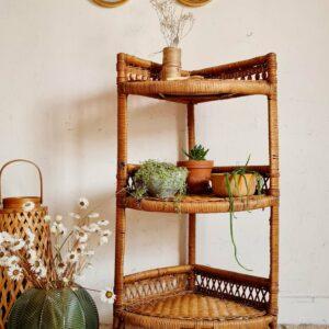 Parfaite dans une chambre d'enfant pour ranger trésors et livres, nous visualisons également cette bibliothèque en rotin vintage dans un angle de la salle de bain ou de la pièce de vie pour y poser des plantes cactées et tombantes.